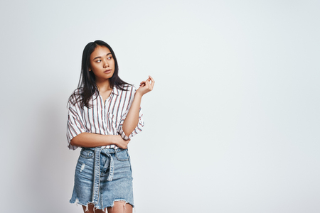 Cute asian young woman in casual wear is thinking what to do and looking away while standing against grey background