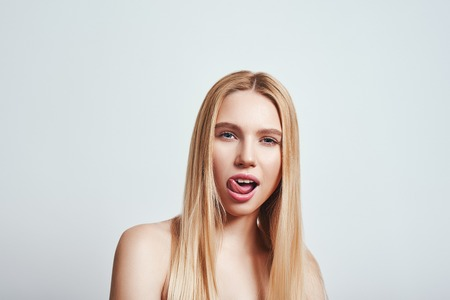 Bad girl. Close-up portrait of playful young woman with long hair looking at camera and sticking out tongue while standing against grey background Banque d'images - 117135392