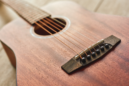 Romantic guitar music...Close up photo of the brown acoustic guitar lying on the wooden floor. Stock Photo