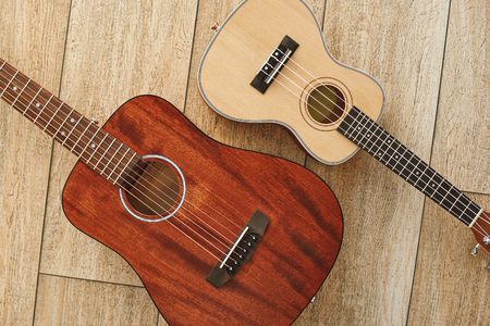 Perfect sound. Top view of the acoustic and ukulele guitars lying close to each other on the wooden floor. Music concept