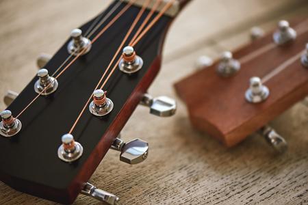 Sound adjusting. Close up photo of guitar necks with tuning keys for adjusting strings against wooden background.