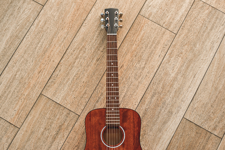 The most elegant instrument. Top view of the brown acoustic guitar lying on the wooden floor.
