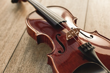 Close up view of beautiful classical violin lying on wooden background. Music background