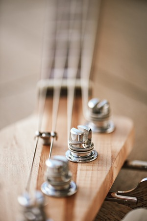 Close-up photo of guitar headstock with keys for adjusting guitar strings.