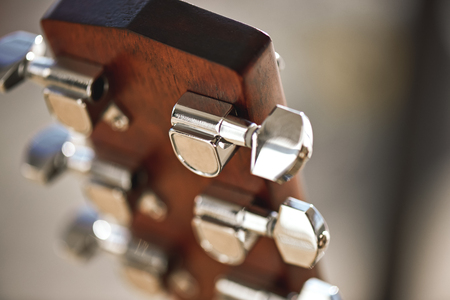 Guitar mechanism. Guitar headstock with focus on string winding mechanism: pegs, strings, vulture.