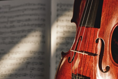 Preparing for a concert. Classic brown violin on music score sheet background. Musical instruments. Stock Photo
