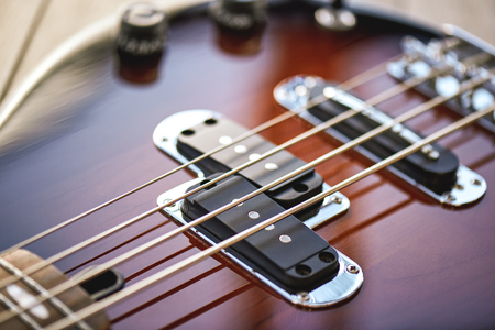 Guitar Lessons. Close-up view of electric guitar body with metal strings, volume and tone controls Stock Photo