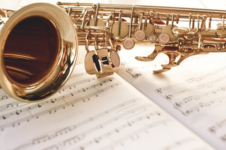 Closeup of a beautiful and shiny golden saxophone lying on music notes.