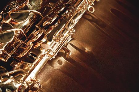 Vue rapprochée et détaillée d'une touche brillante d'un saxophone doré allongé sur un canapé en cuir. Instruments de musique.