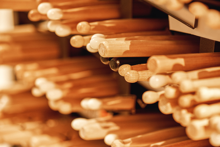 Preparing for a concert. A lot pairs of professional wooden drum sticks laying on the shelves in music studio. Stock Photo