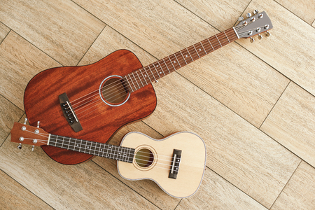Musical instruments background. Top view of the acoustic and ukulele guitars lying close to each other against the wooden floor. Stock Photo