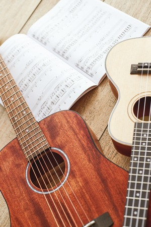 Learning how to play guitar. Vertical close up photo of acoustic and ukulele guitars lying on the wooden floor with music notes.