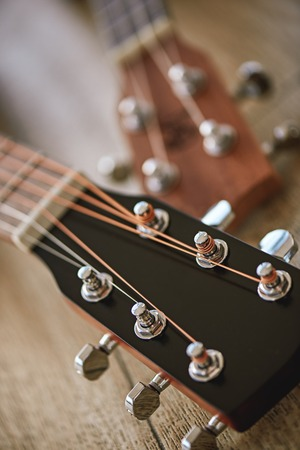 Uppermost part of the guitar. Vertical close up photo of guitar necks with tuning keys for adjusting strings against wooden background