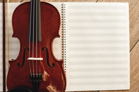 Composing for the violin. Top view of beautiful brown violin lying on sheets for music notes.
