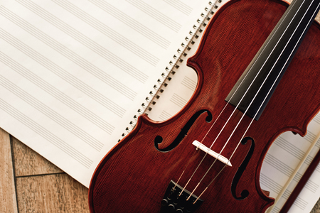 Writing Violin Music. Close up view of beautiful brown violin lying on sheets for music notes. Musical instruments. Stock Photo