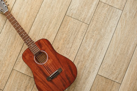 Beauty of musical instrument. Top view of the brown acoustic guitar lying on the wooden floor.