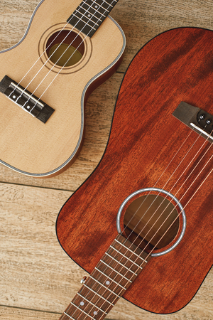 Music from heart. Vertical top view of the acoustic and ukulele guitars lying close to each other on the wooden floor Stock Photo