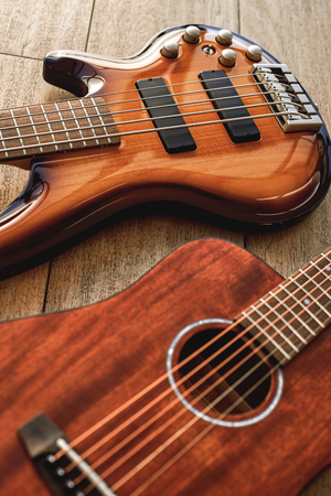 Choosing a guitar...Top view on two perfect polished musical instruments: acoustic and electric guitars are lying on the wooden floor in a music shop