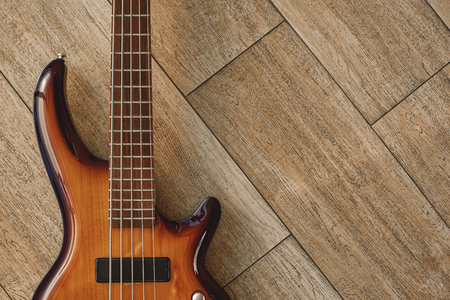 Power of musical instrument. Top view of the brown electric guitar lying on the wooden floor.