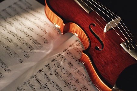 How to Read Violin Notes? Close up view of brown wood violin lying on the sheet with music notes. Stock Photo