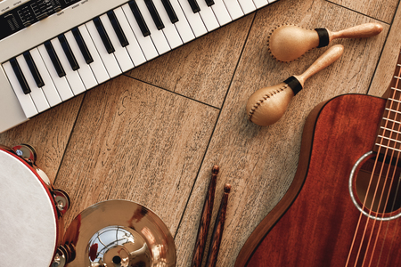 Creating a melody...Top view of musical instruments set: synthesizer, electronic guitar, wooden drum sticks, golden cymbal, drums, gold maracas and tambourine lying on wooden background. 版權商用圖片