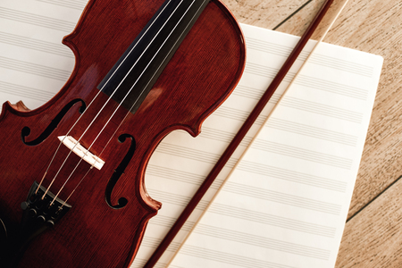 Art of Composing. Close up view of brown violin with a bow lying on sheets for music notes