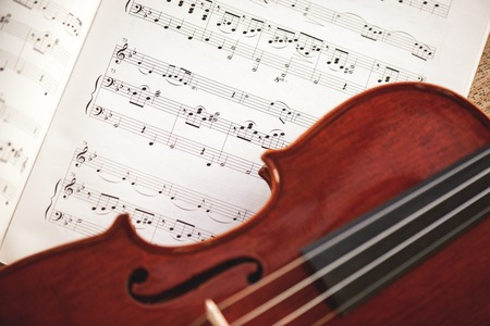 In love with classic music. Close up view of brown violin lying on music score sheet. Violin lessons 写真素材