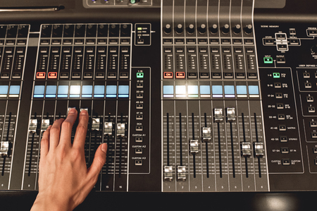Professional sound control. Close-up view of male hand mixing sounds on digital audio mixing console with many buttons and shaders.