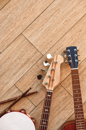 Top view of musical instruments: guitars, drums with sticks lying on light wooden background Stock Photo