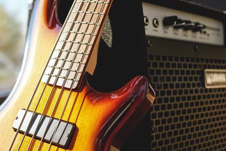 Gitarre spielen. Nahaufnahme der braunen E-Gitarre und des Verstärkers.