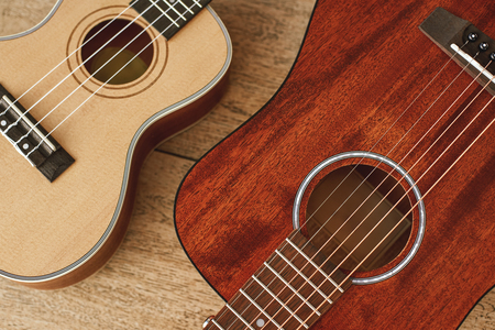 Ideal musical pair. Top view of the acoustic and ukulele guitars lying close to each other on the wooden floor. Stock Photo
