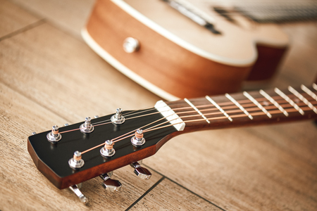 Tuning sound. Close view of guitar neck with tuning keys for adjusting guitar strings lying on the wooden floor