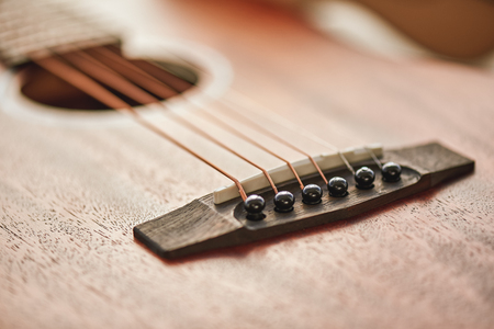 Sound adjusting. Close up detailed photo of guitar strings and sound hole.