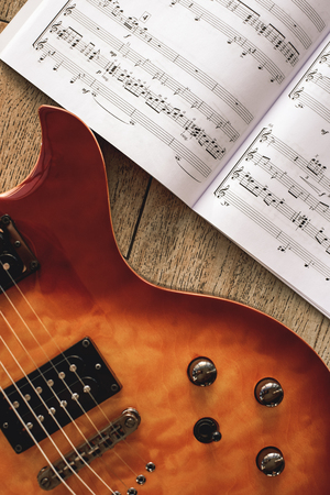 Electric Guitar Chords. Close-up photo of electric guitar body with volume and tone control knobs with music notes against of wooden background. Banco de Imagens