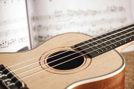Ukulele chords. Close-up photo of ukulele guitar and music notes against of wooden background. Musical instruments. Music equipment Archivio Fotografico - 117239012