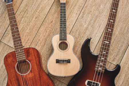 How To Choose Your First Guitar? Top view on three different types of guitars: acoustic, electric and ukulele. Stok Fotoğraf