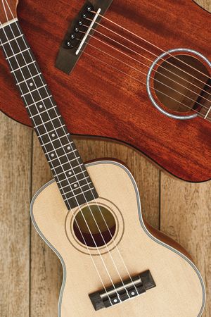 Guitar theme. Vertical top view of the acoustic and ukulele guitars lying on each other against the wooden floor.