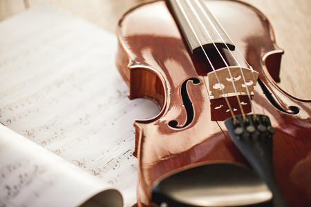 Beauty of musical instruments. Close up view of brown violin lying on sheets with music notes on wooden floor. Violin lessons. Musical instruments. Music equipment. Stockfoto