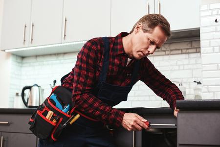 Handyman at work. Repairing kitchen shelves by screwdriver