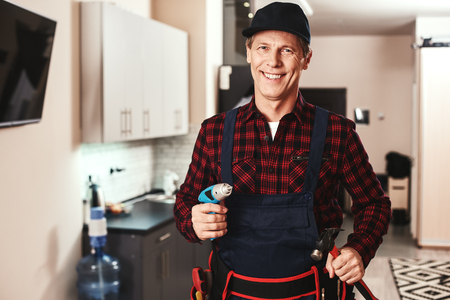 Cheerful handyman. Portrait of a smiling male foreman standing with equipment