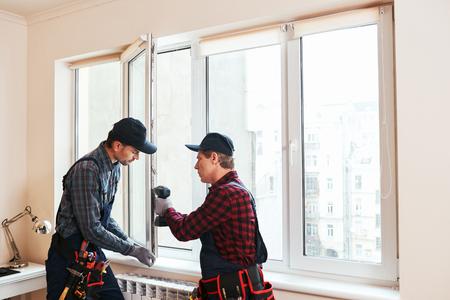 Qualitätslicht. Bauarbeiter bauen gemeinsam ein neues Fenster im Haus ein