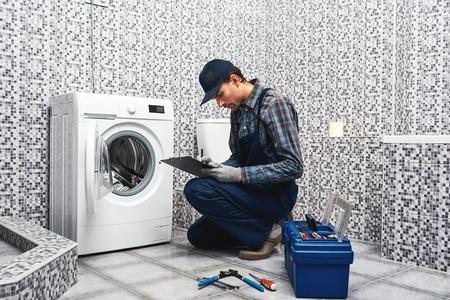 Price of plumbers work. Working man plumber writing price list Standard-Bild - 117135756