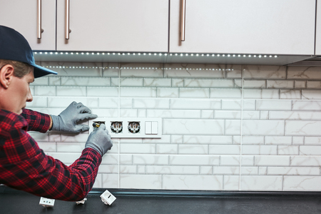 All is safe. Rear view of senior handyman setting new sockets Stock Photo