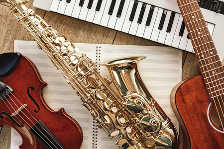 Poder de la música. Vista superior del conjunto de instrumentos musicales: sintetizador, guitarra, saxofón y violín en las hojas para notas musicales sobre piso de madera