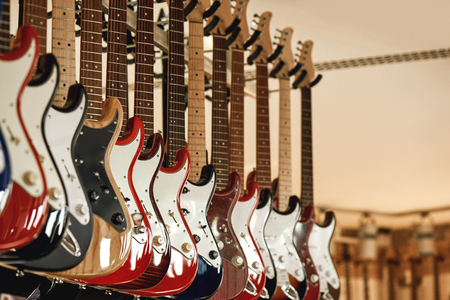 Buying electric guitar. Stand with various colorful electric guitars in music shop. Musical instrument. Musical instrument store Stock Photo