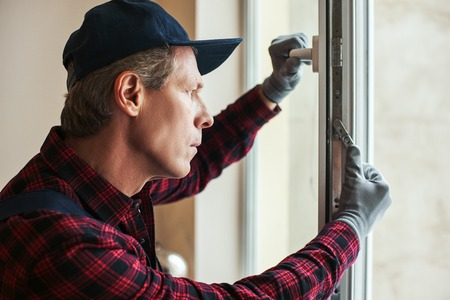 Sensitive settings. Close-up of senior handyman setting new windows