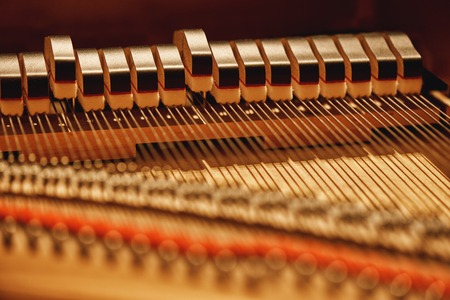 Inside of a piano. Close-up view of hammers and strings inside the piano. Musical instruments