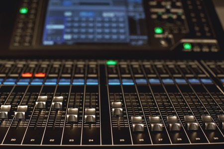 Digital Audio mixing console. Close-up view of professional equipment for sound mixing. Focus on audio control buttons