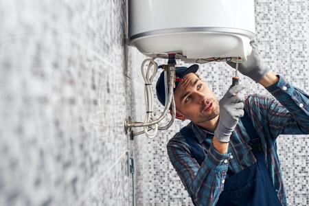 Fast fertig. Arbeiter richten elektrischen Heizkessel im Badezimmer zu Hause ein