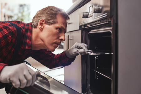 He knows how to solve this problem. Close-up of repairman examining oven